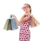 Το όμορφο μικρό κορίτσι με την τσάντα αγορών, πορτρέτο στούντιο, έντυσε στο ροζ με τις μορφές καρδιών, άσπρο υπόβαθρο Στοκ Φωτογραφία