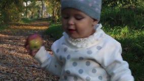 Το όμορφο μικρό κορίτσι με το μήλο πηγαίνει στην πορεία στο φθινόπωρο φιλμ μικρού μήκους