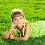 Το όμορφο μικρό κορίτσι μιλά σε ένα τηλέφωνο και βρίσκεται σε ένα πράσινο στοκ εικόνες
