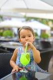 Το όμορφο μικρό κορίτσι πίνει τη λεμονάδα με τη μέντα χρησιμοποιώντας το άχυρο Στοκ Φωτογραφία