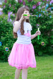 Το όμορφο μικρό κορίτσι παίζει με τις φυσαλίδες σαπουνιών Στοκ Εικόνα