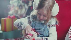 Το όμορφο μικρό κορίτσι παίρνει τα δώρα από τα κιβώτια Χριστουγέννων φιλμ μικρού μήκους