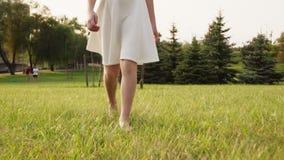 Το όμορφο μικρό κορίτσι πηγαίνει χωρίς παπούτσια στη χλόη στο ηλιόλουστο θερινό πάρκο απόθεμα βίντεο