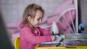 Το όμορφο μικρό κορίτσι στη ρόδινη ζακέτα σύρει την απεικόνιση με τα χρωματισμένα μολύβια στον παιδικό σταθμό Μικρός ταλαντούχος απόθεμα βίντεο