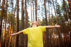 Το όμορφο μικρό κορίτσι στο δάσος πεύκων με τα χέρια απολαμβάνει επάνω τη φύση στοκ φωτογραφία