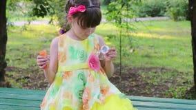 Το όμορφο μικρό κορίτσι φυσά τις φυσαλίδες και το πιάνει στον πάγκο στο πράσινο πάρκο στη θερινή ημέρα απόθεμα βίντεο