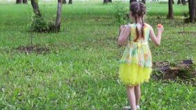 Το όμορφο μικρό κορίτσι φυσά τις φυσαλίδες στο πράσινο πάρκο στη θερινή ημέρα φιλμ μικρού μήκους