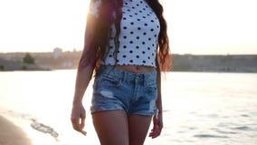 Το όμορφο μοντέρνο ευτυχές μοντέρνο νέο όμορφο κορίτσι περιπάτους στους άσπρους χαριτωμένους καπέλων κατά μήκος της παραλίας, στη φιλμ μικρού μήκους