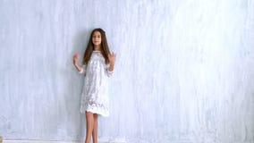 Το όμορφο μοντέρνο κορίτσι θέτει σε ένα γκρίζο υπόβαθρο φιλμ μικρού μήκους