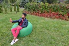 Το όμορφο νέο αραβικό άτομο κρατά στα χέρια που το κινητό τηλέφωνο, καλεί επάνω Στοκ Εικόνα