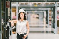 Το όμορφο νέο ασιατικό χαμόγελο γυναικών μηχανικών ή τεχνικών, η αποθήκη εμπορευμάτων ή το εργοστάσιο θολώνουν το υπόβαθρο, τη βι στοκ φωτογραφία με δικαίωμα ελεύθερης χρήσης