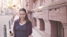 Το όμορφο νέο εύθυμο κορίτσι περπατά στην πόλη Τρεξίματα που ταλαντεύονται τα χέρια του Ακούει τη μουσική στα ακουστικά φιλμ μικρού μήκους