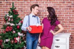 Το όμορφο νέο ζεύγος γιορτάζει τα Χριστούγεννα στο σπίτι Παρόν δώρο φίλων το κορίτσι του Εξετάστε ο ένας τον άλλον μάτια στοκ φωτογραφία