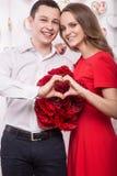 Το όμορφο νέο ζεύγος ερωτευμένο με μια ανθοδέσμη ανθίζει την παρουσίαση της μορφής χεριών καρδιών συνδεδεμένο διάνυσμα βαλεντίνων Στοκ φωτογραφία με δικαίωμα ελεύθερης χρήσης