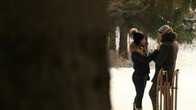 Το όμορφο νέο ζεύγος ξοδεύει το χρόνο στο χειμερινό πάρκο απομονωμένη Χριστούγεννα διάθεση τρία σφαιρών λευκό Το αγόρι και το κορ απόθεμα βίντεο