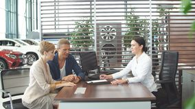 Το όμορφο νέο ζεύγος υπογράφει τα έγγραφα στο γραφείο εμποριών αυτοκινήτων φιλμ μικρού μήκους