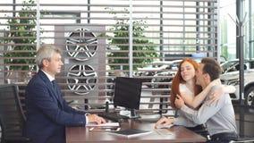Το όμορφο νέο ζεύγος υπογράφει τα έγγραφα στο γραφείο εμποριών αυτοκινήτων απόθεμα βίντεο