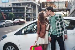 Το όμορφο νέο ζεύγος φιλά κοντά σε ένα αυτοκίνητο, κάνει αγορές στοκ φωτογραφία