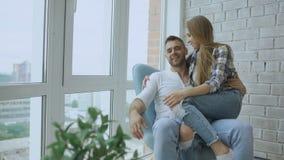 Το όμορφο νέο ζεύγος χαλαρώνει τη συνεδρίαση στην καρέκλα και την απόλαυση της θέας από το μπαλκόνι του νέου διαμερίσματος σοφιτώ απόθεμα βίντεο