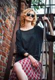 Το όμορφο νέο κορίτσι βράχου grunge που φορά τη φούστα, την μπλούζα και τα γυαλιά καρό κάθεται στο κλιμακοστάσιο Στοκ Εικόνα