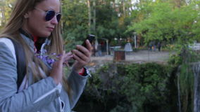 Το όμορφο νέο κορίτσι γράφει ένα μήνυμα για να χρησιμοποιήσει ένα smartphone στα πλαίσια ενός καταρράκτη το καλοκαίρι και φιλμ μικρού μήκους