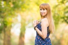 Το όμορφο νέο κορίτσι γύρισε και ανέτρεξε με ένα χαμόγελο στο πλαίσιο στο υπόβαθρο της ηλιόλουστης θολωμένης πρασινάδας Στοκ φωτογραφία με δικαίωμα ελεύθερης χρήσης