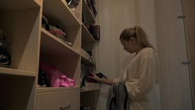 Το όμορφο νέο κορίτσι επιλέγει μια τσάντα στο βεστιάριο της φιλμ μικρού μήκους