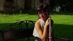 Το όμορφο νέο κορίτσι κάθεται σε έναν πάγκο με ένα βιολί στο όμορφο πάρκο φιλμ μικρού μήκους
