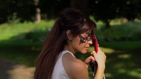Το όμορφο νέο κορίτσι κάθεται σε έναν πάγκο με ένα βιολί στο όμορφο πάρκο απόθεμα βίντεο