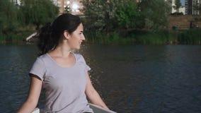 Το όμορφο νέο κορίτσι κάθεται σε μια βάρκα φιλμ μικρού μήκους