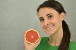 Το όμορφο νέο κορίτσι κρατά ένα κόκκινο γκρέιπφρουτ Στοκ Φωτογραφίες