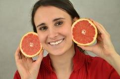 Το όμορφο νέο κορίτσι κρατά ένα κόκκινο γκρέιπφρουτ Στοκ εικόνα με δικαίωμα ελεύθερης χρήσης