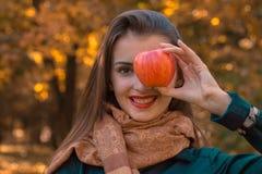 Το όμορφο νέο κορίτσι κρατά τη Apple στο πρόσωπο και χαμογελά στο krupnyy σχέδιο Στοκ Φωτογραφία