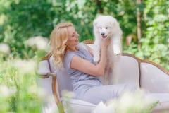 Το όμορφο νέο κορίτσι με ένα άσπρο κουτάβι στα όπλα της και τα παλαιότερα λευκά χνουδωτά σκυλιά σε έναν αναδρομικό καναπέ ένα καλ Στοκ φωτογραφία με δικαίωμα ελεύθερης χρήσης