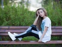 Το όμορφο νέο κορίτσι με μακρυμάλλη κάθεται σε έναν πάγκο στα παπούτσια γυμναστικής και μια μπλούζα Στοκ Εικόνα