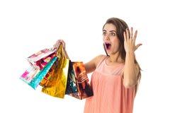 Το όμορφο νέο κορίτσι με τη μεγάλη έκπληξη κρατά διαθέσιμες πολλές διαφορετικές χρωματισμένες αγορές συσκευασιών Στοκ Εικόνες
