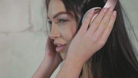 Το όμορφο νέο κορίτσι ντύνει το ακουστικό σε σε αργή κίνηση απόθεμα βίντεο
