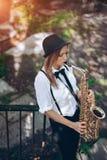 Το όμορφο νέο κορίτσι παίζει ένα saxophone στεμένος στα βήματα - υπαίθρια Η ελκυστική γυναίκα στην άσπρη έκφραση πουκάμισων παίζε Στοκ φωτογραφία με δικαίωμα ελεύθερης χρήσης