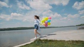 Το όμορφο νέο κορίτσι παρουσιάζει ευτυχείς συγκινήσεις με τα μπαλόνια διαθέσιμα στο coustline φιλμ μικρού μήκους