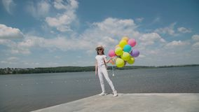 Το όμορφο νέο κορίτσι παρουσιάζει ευτυχείς συγκινήσεις με τα μπαλόνια διαθέσιμα στο coustline απόθεμα βίντεο