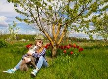 Το όμορφο νέο κορίτσι σε έναν κήπο αγκαλιάζει ένα σκυλί Στοκ Φωτογραφία