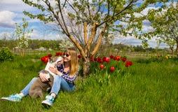 Το όμορφο νέο κορίτσι σε έναν κήπο αγκαλιάζει ένα σκυλί Στοκ εικόνες με δικαίωμα ελεύθερης χρήσης