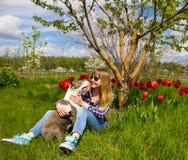 Το όμορφο νέο κορίτσι σε έναν κήπο αγκαλιάζει ένα σκυλί Στοκ φωτογραφία με δικαίωμα ελεύθερης χρήσης