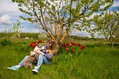 Το όμορφο νέο κορίτσι σε έναν κήπο αγκαλιάζει ένα σκυλί Στοκ Εικόνα