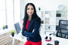 Το όμορφο νέο κορίτσι σε ένα επιχειρησιακό κοστούμι στέκεται στο γραφείο, που κλίνει σε έναν πίνακα Στοκ Εικόνα
