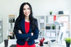 Το όμορφο νέο κορίτσι σε ένα επιχειρησιακό κοστούμι στέκεται στο γραφείο, που κλίνει σε έναν πίνακα Στοκ Εικόνες