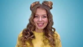 Το όμορφο νέο κορίτσι σε ένα κίτρινο πουκάμισο είναι έκπληκτο και χαμογελώντας εξετάζοντας τη κάμερα φιλμ μικρού μήκους