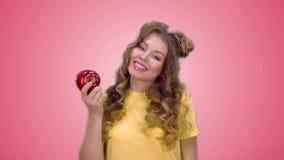 Το όμορφο νέο κορίτσι σε ένα κίτρινο πουκάμισο κάνει μια επιλογή υπέρ των υγιών προϊόντων σε ένα ρόδινο υπόβαθρο απόθεμα βίντεο