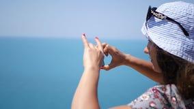 Το όμορφο νέο κορίτσι σε ένα καπέλο πυροβολεί ένα πανόραμα της θάλασσας στο τηλέφωνο HD, 1920x1080 κίνηση αργή απόθεμα βίντεο