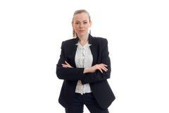 Το όμορφο νέο κορίτσι σε ένα μαύρο επιχειρησιακό κοστούμι στέκεται με τα διπλωμένα χέρια και το κοίταγμα άμεσα Στοκ εικόνα με δικαίωμα ελεύθερης χρήσης